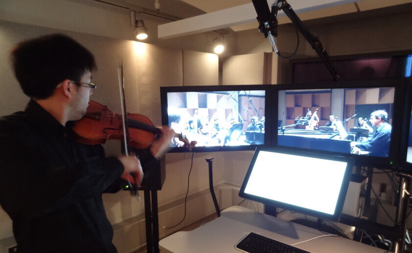 A violinist plays within a virtual orchestra