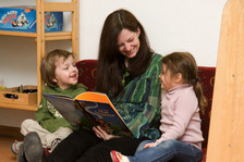 Childcare provider look at a book with a child